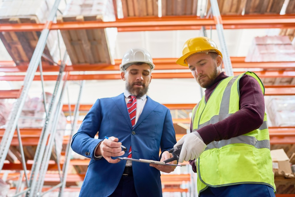 Waist up portrait of mature businessman talking to warehouse worker, discussing inventory on clipboard